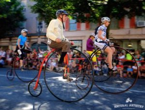 Two people on high-wheel bikes racing in the National Clustered Spires High Wheel Race
