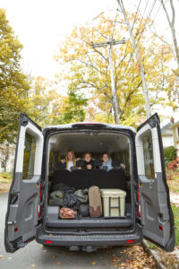 A family in the back of the van with trunk doors open and luggage inside