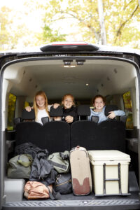 Landbird passengers in the back seat looking out at an open trunk with gear in it